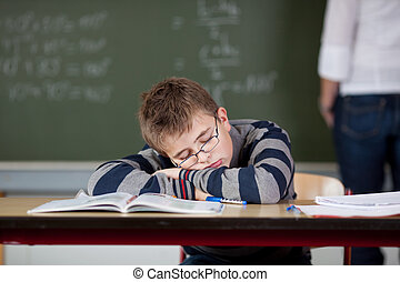 Student Sleeping At Desk While Teacher Standing In...