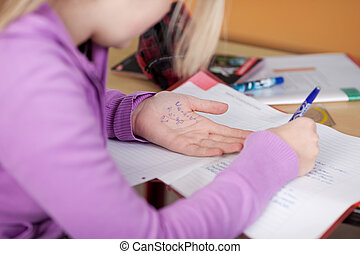 Student Copying From Cheat Sheet On Hand At Desk -...