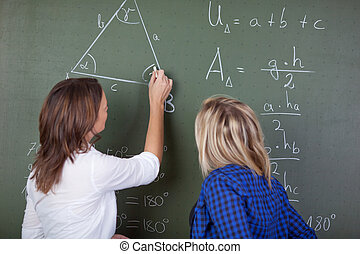 Teacher solving a mathematics question - Female teacher...