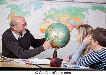 Teacher Pointing At Globe While Students Looking At It -...