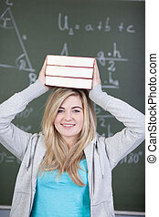 Happy female student carrying stacked books on head against...