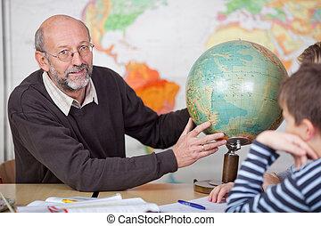 Teacher teaching the class about geography - An elderly...