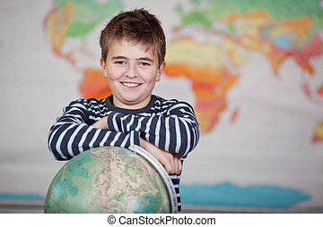 Preadolescence Child Leaning On Globe In Classroom -...