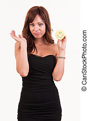 Sad young woman holding object with happy smiley