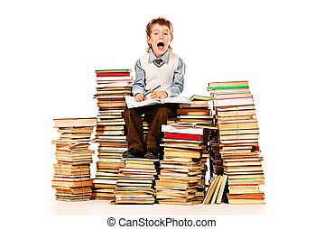 examination stress - A boy sitting on a pile of books and...