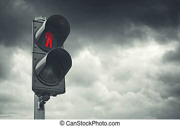 Red traffic light for pedestrians against gray cloudy sky.