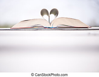 God is love ! - Bible on the table with heart shaped pages....