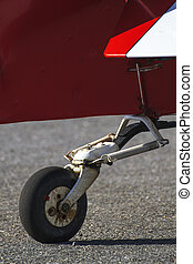 wheel of a red propeller airplane