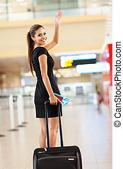 businesswoman waving goodbye at airport - cheerful...