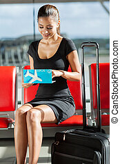 businesswoman checking her flight ticket - smiling...