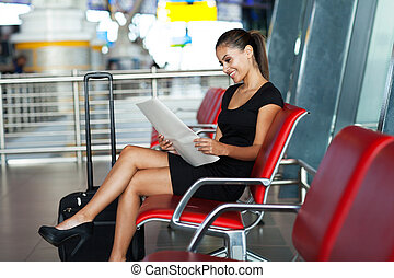 young businesswoman reading newspaper at airport - smiling...