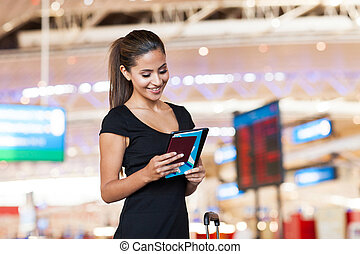 businesswoman at airport reading her emails on tablet...