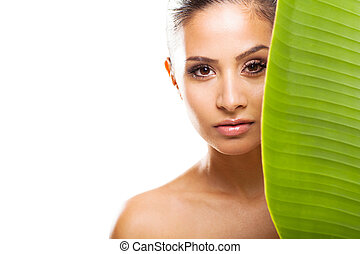 fresh clear face of young woman behind green leaf