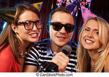 Singing at party - Group of friends singing in microphone in...