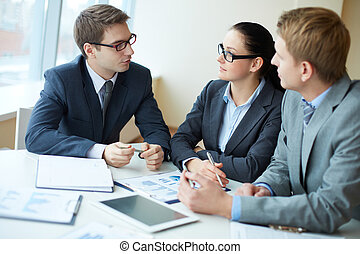 Negotiations - Image of three business people negotiating at...