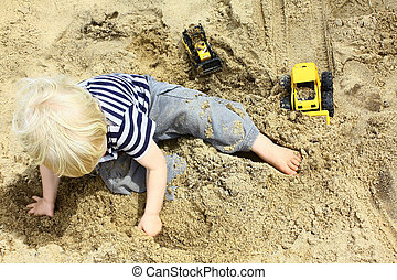 Child Playing Trucks in Sandbox - A young boy plays with toy...