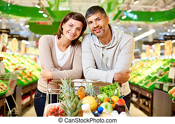 Buying products - Image of happy couple with cart full of...