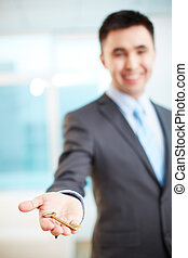 Giving key - Hand of businessman holding key