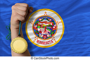 Winner holding gold medal for sport and flag of us state of minnesota