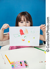 Girl Showing Drawing Paper In Classroom - Portrait of little...