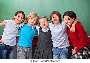 Portrait of cute little schoolchildren with arms around...