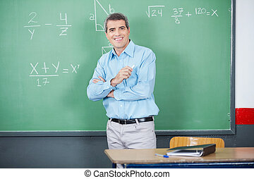 Male Teacher Standing Arms Crossed Against Board - Portrait...