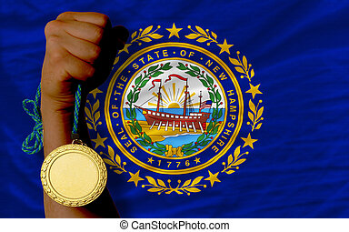 Winner holding gold medal for sport and flag of us state of new hampshire