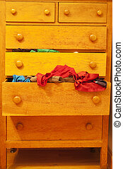 A wooden dresser with a drawer overflowing with clothes