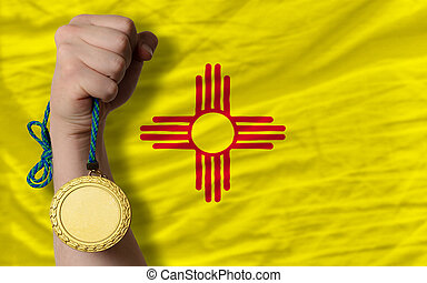 Winner holding gold medal for sport and flag of us state of new mexico