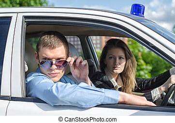 Two young detectives driving to crime scene