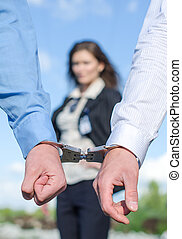 Close up view of hands in handcuffs and female FBI agent on background