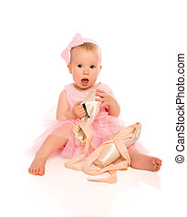 Little baby girl in a pink ballerina dress with pointe shoes...