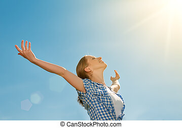 happy young woman open her arms to the sky