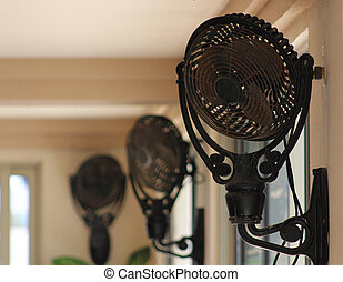 Rusty Fans - Three vintage fans mounted near the ceiling to...