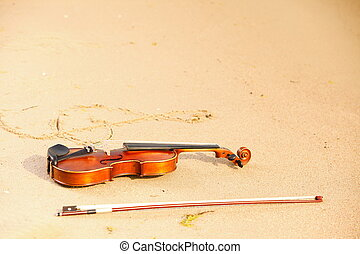 Violin and g clef on beach. Music concept - Violin string...