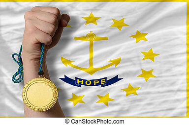 Winner holding gold medal for sport and flag of us state of rhode island