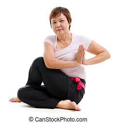 Asian senior woman practicing yoga, isolated on white...