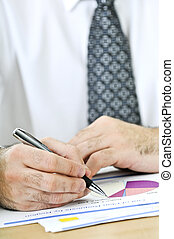 Office worker writing on reports - Office worker reviewing...