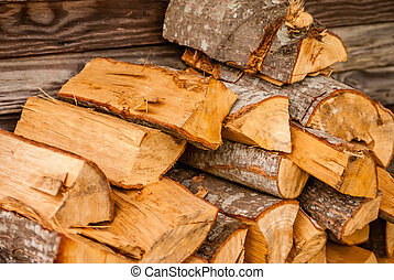 chopped fire wood next to log cabin ready for winter
