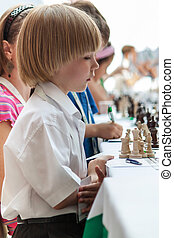 Young boy plays chess - Young boy playing chess on the...