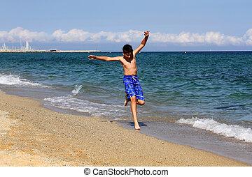Boy running on the sea beach on summer holidays
