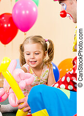 happy kid girl and clown on birthday party