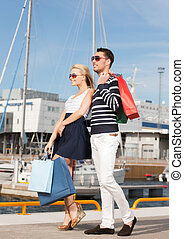 young couple in duty free shopping bags - picture of happy...