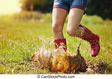 Woman have fun jumping in puddle