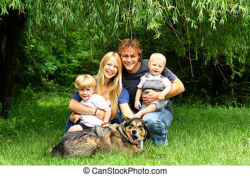 Happy Family Sitting Under Willow Tree - A happy family of...