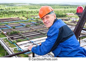 Caucasian mature manual worker in blue uniform and orange hardhat looking back
