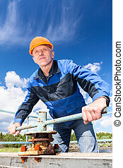 Mature Caucasian worker in a hardhat at the factory with the pipe valve