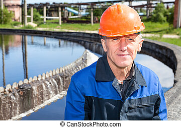 Caucasian senior manual worker sitting near water filtration...