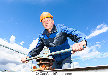 Mature worker - Senior Caucasian worker in a hardhat at the...