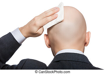 Hand holding tissue wiping or drying bald sweat head - Tired...